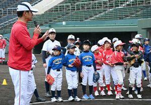 緒方孝市さん(左)の話に耳を傾ける子どもたち=佐賀市のみどりの森県営球場