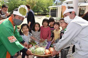 野菜や果物をもらって喜ぶ大里保育園の園児=伊万里市二里町