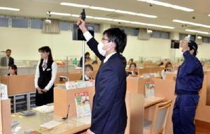拳銃を示して現金を要求する強盗犯役の署員(中央)=鳥栖市の佐賀銀行鳥栖支店