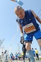 好天で気温もぐんぐん上昇。頭から勢いよく水をかけてもらいクールダウン=神埼市神埼町の給水所