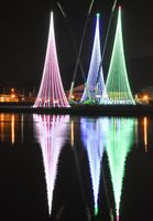 松浦川の川面に映る巨大ツリー。奥の屋根は唐津東中高の体育館=19日夕、唐津市文化体育館側の川岸から撮影