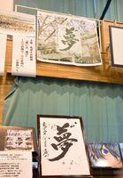 書家・江島史織さんが書いた「夢」(下)の背景に桜と校舎を描いたモザイクアート(上)=佐賀市の金泉中学校