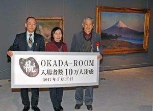 「OKADA―ROOM」の来場10万人目となった松本健太さん(右端)と妻・秀子さん(中央)=佐賀市の県立美術館