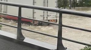冠水した国道34号を白波を立てて走るトラック=武雄市北方町志久(14日午前6時58分、読者提供写真)