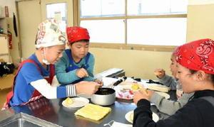 キャラメルフォンデュをビスケットにつけて試食する児童たち=伊万里市の大坪小