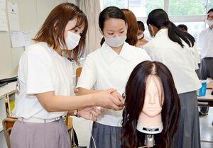 専門学校生の指導で、ヘアアイロンを使ってウェーブをつくる体験をする生徒=有田町の有田工高