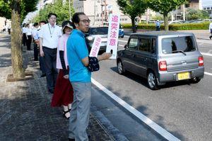 「追突注意」のハンドポップを掲げ、安全運転を呼びかける県警と県職員=佐賀市の県警本部前