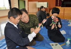 老人クラブの会員らに教わりながら、しめ縄飾りを作る子どもたち=三根東小学校