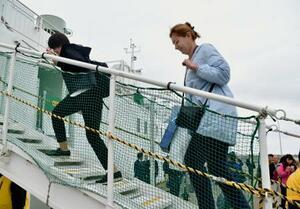 共同経済活動に向けた視察を終え、帰路の船に乗り込むロシア側視察団員(右)=23日午前、北海道根室市