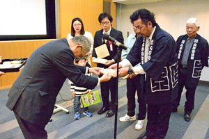 表彰式で木製の盾を受け取る受賞者(右)=佐賀市の佐賀市立図書館