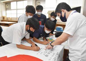 東京五輪に出場するサガン鳥栖の林大地選手への応援メッセージを寄せ書きするサッカー部員たち=鳥栖市の鳥栖中