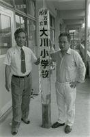 戻ってきた学校の標柱を手に感慨深げな西川校長(左)と毛利教頭=平成2年7月23日、伊万里市の大川小