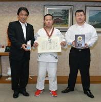 賞状を持ち、横尾俊彦市長(左)と一緒に記念撮影に写る岡島龍太郎君。右は父親の洋一郎さん=多久市役所