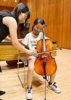 佐賀交響楽団のメンバーから指導を受け、チェロの演奏に挑戦する児童=佐賀市文化会館