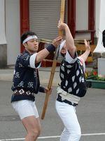 演技中に竹竿を手際よくつなげていく男衆=武雄市の武雄温泉楼門前