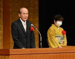 金婚さんの表彰を受け、あいさつする松﨑逸夫さん(左)美弥子さん夫妻=佐賀市文化会館
