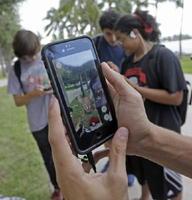 スマートフォン向けゲーム「ポケモンGO」で遊ぶ人たち=12日、米フロリダ州マイアミ(AP=共同)