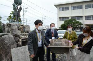 像の台座からタイムカプセルを取り出し運ぶ卒業生ら=佐賀市の嘉瀬小
