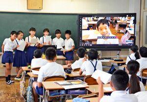 画面越しに感想を伝える東脊振小の児童と、それを見守る三田川小の児童たち=吉野ヶ里町の三田川小