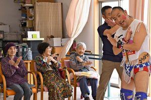 プロレスラーの「ばってん×ぶらぶら」さん(右)と一緒にポーズを取る利用者たち=佐賀市の有料老人ホーム・デイサービスセンター「花梨」