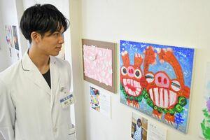 「はーとあーと俱楽部」のメンバーが制作した絵画を眺める齋田航さん=佐賀市金立町のアサヒ薬局