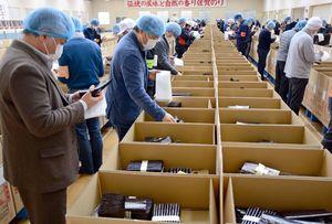 最終入札会に出品された秋芽ノリの品質をチェックする商社の担当者=佐賀市の佐賀海苔共販センター
