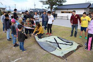 テントの設営を学ぶ参加者たち=神埼市神埼町の長崎街道門前広場(提供)
