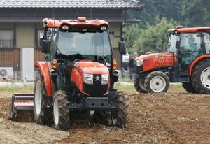 クボタが試験販売する自動運転トラクター(左)=31日、茨城県桜川市(同社提供)