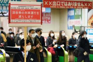 新宿駅で終電近くの一部列車の運休を知らせるJR東日本の社員=19日午前