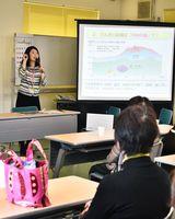 「電気は大量にためることができず、使う分だけ発電している」と説明する麻生恵美さん(左奥)=神埼市のJAさが神埼千代田支所