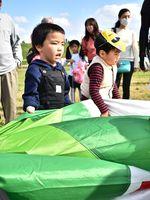 気球教室で球皮の片付けの手伝いをする子どもたち=佐賀市の嘉瀬川河川敷