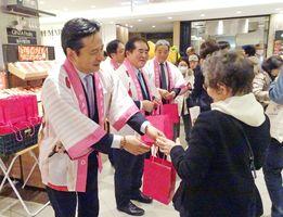 佐賀フェアで買い物客に「さがほのか」のパックをプレゼントする山口祥義知事=東京・銀座三越