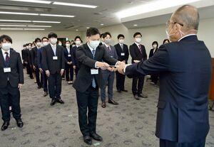 代表して辞令書を受け取る坂井悠太さん。コロナ対策のため、新規採用職員を二つに分けて式を実施した=佐賀市役所