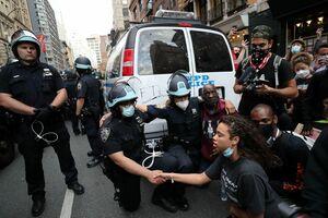 デモ参加者と一緒に地面に片膝をついて共感を示す警官ら=2日、米ニューヨーク(ロイター=共同)