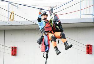 ロープを使って、建物などに孤立した要救助者の元に向かう救助隊員=佐賀市の県消防学校