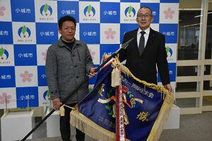 8年連続で手にした優勝旗を江里口秀次小城市長(右)に手渡した野田正一郎監督=市役所