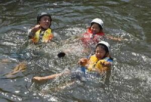石井樋で川の流れに身を任せて楽しむ参加者=佐賀市大和町