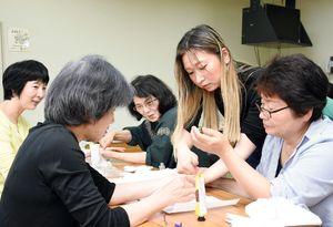嘉村恵美子さん(右2人目)からハンドマッサージの技術を教わる受講生たち=吉野ヶ里町の三田川健康福祉センター