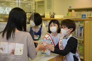 カウンターで本の貸し出しを体験する嘉瀬小4年の津川大騎君(右)と村松真菜さん=佐賀市立図書館