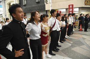 肩を組んで早稲田大校歌を熱唱する学生ら=佐賀市の白山名店街