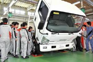 贈呈されたトラックを囲み、構造などを確認する生徒ら=佐賀市の佐賀工業専門学校