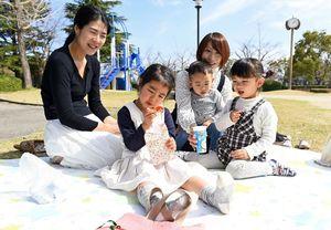 陽気の中で芝生にシートを敷き、おやつを広げる親子連れ=佐賀市城内のシャボン玉公園