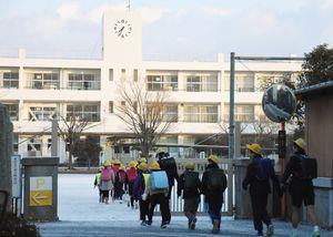 雪がうっすらと積もる中、登校する千代田中部小学校の児童=6日午前7時35分ごろ、神埼市千代田町の同校