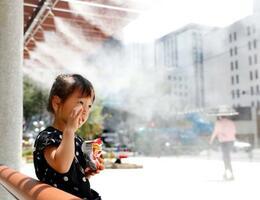 厳しい暑さの中、ドライミストの下で涼む女の子=5日午後、東京・銀座