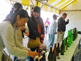 肥前いろは祭で各蔵元の酒を試飲する来場者=12日、肥前市民センター