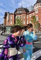 厳しい日差しの中、浴衣を着て歩く女性=19日午後、東京・丸の内