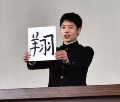 漢字を書いた色紙を持って決意を語る生徒=佐賀市の城東中学校