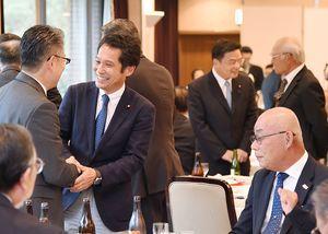 武雄市内で開かれた叙勲祝賀会で、出席者と声を交わす古川康氏(右奥から2人目)と大串博志氏(左から2人目)=23日午後