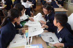 6紙が同じ日に発行した紙面の1面を見比べて佐賀新聞を探す千代田西部小5年1組の子どもたち=神埼市の千代田西部小