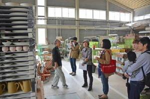 普段は入れない有田焼の製造工場を開放する工場マルシェ。参加者が興味深げに工場内を見学した=昨年11月、有田町